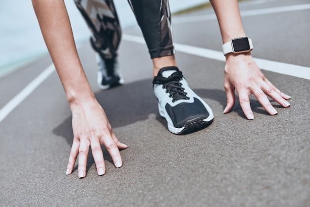 Изо всех сил. крупным планом молодой женщины в спортивной одежде, стоящей на стартовой линии