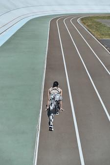 Делает все возможное. вид сверху сзади молодой женщины в спортивной одежде, стоящей на стартовой линии