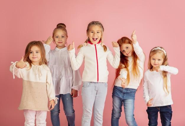 Дарить и получать подарки на рождественские праздники. группа счастливых улыбающихся детей, весело проводящих время, празднуя изолированные на розовом фоне студии. встреча нового 2021 года, детство, счастье, эмоции.
