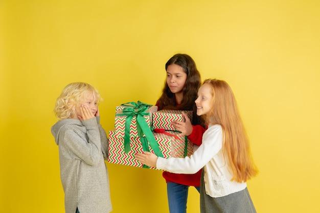 Дарить и получать подарки на рождественские праздники. группа счастливых улыбающихся детей, весело проводящих время