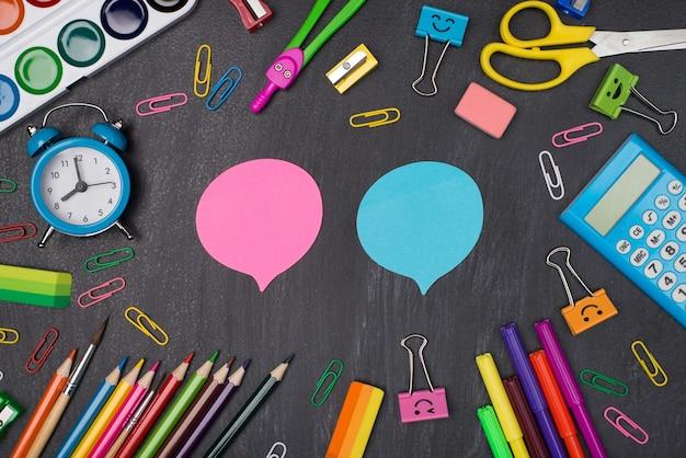 의견 및 의견 개념을 제공합니다. 칠판에 격리된 두 개의 분홍색 및 파란색 거품 주위에 있는 다채로운 편지지의 상단 보기 사진