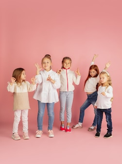 Giving and getting presents on christmas holidays. group of happy smiling children having fun, celebrating isolated on pink studio background. new year 2021 meeting, childhood, happiness, emotions.