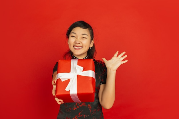 Giving giftbox. happy chinese new year 2020. asian young girl's portrait isolated on red background. female model in traditional clothes looks happy. celebration, holiday, emotions. copyspace.