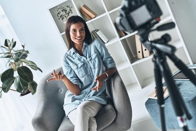 良いアドバイスをする。屋内で新しいビデオを作成しながら身振りで示すと笑顔の魅力的な若い女性