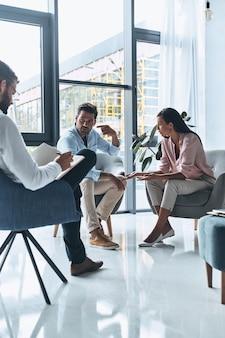 Давать хороший совет. молодая супружеская пара разговаривает, сидя на сеансе терапии