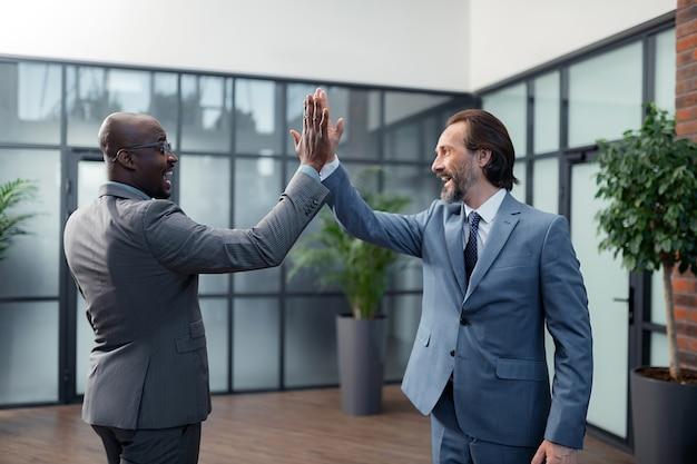 ハイタッチをする。交渉が成功した後、ハイタッチをする2人の陽気な金持ちのビジネスマン