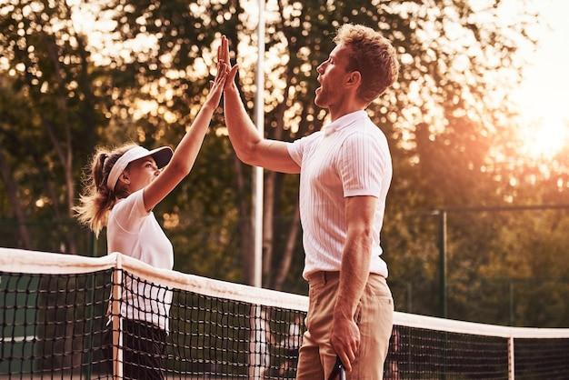 ハイタッチをする。スポーツユニフォームを着た二人がコートで一緒にテニスをします。