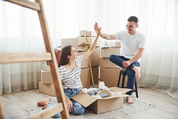 Дай пять. мы сделали это. веселая молодая пара в своей новой квартире. концепция переезда.