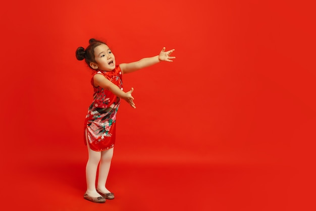 Dare un abbraccio ad amici e parenti. . bambina sveglia asiatica isolata sulla parete rossa in vestiti tradizionali. celebrazione, emozioni umane, concetto di vacanze. copyspace.
