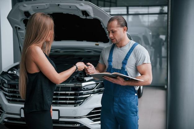キーを与える。修理の結果。彼女の車がどのような被害を受けたかを示す自信を持った男性