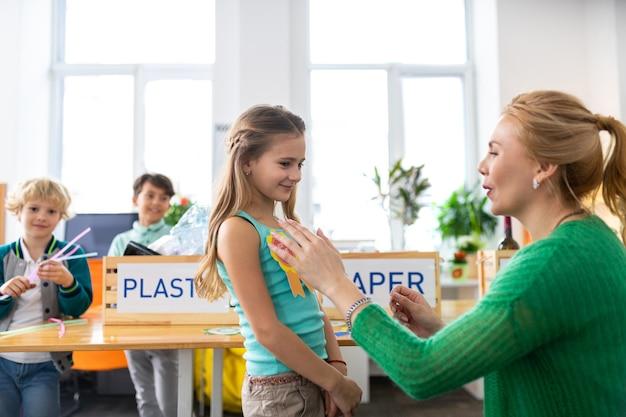 小さなメダルを与える。環境にやさしいためにかわいいスマートな女の子に小さなメダルを与えるブロンドの髪の先生