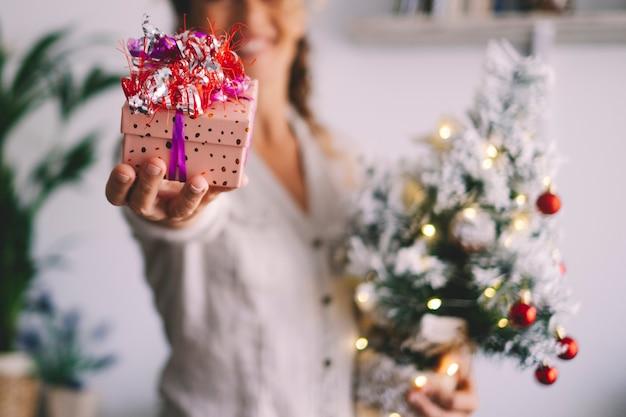 クリスマスイブの休日とバックグラウンドで女性にプレゼントを贈る