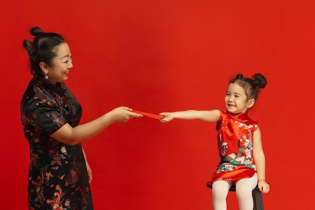 赤い封筒と笑顔を与えます。 。伝統的な服の赤い壁に分離されたアジアの母と娘の肖像画。お祝い、人間の感情、休日。コピースペース。