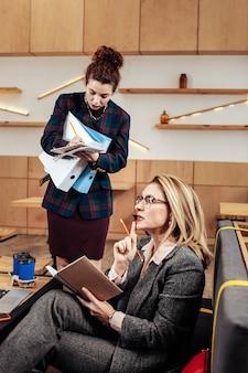 タスクを与える。若い有能な秘書に仕事を与える金髪の忙しい魅力的なビジネスウーマン