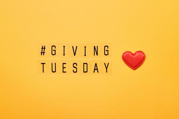 火曜日にテキストメッセージを送信します。ブラックフライデーの買い物日の後の慈善寄付の世界的な日。黄色の背景に赤いハート。