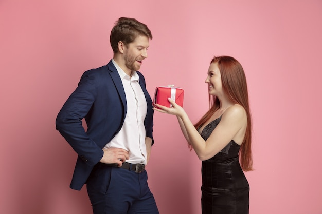 Giving you a gift and emotions. valentine's day celebration, happy caucasian couple on coral background. concept of human emotions, facial expression, love, relations, romantic holidays.