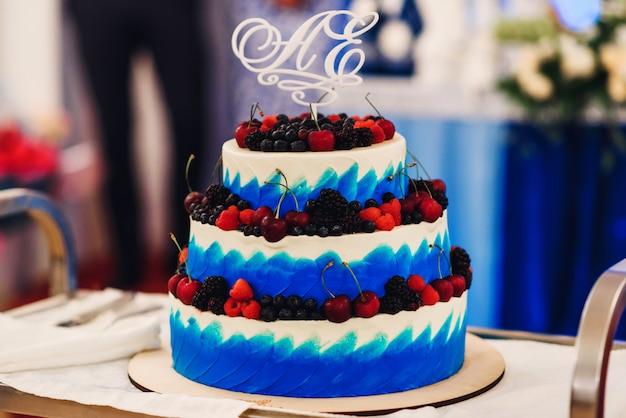 新鮮なベリーチェリー、ブルーベリー、ブラックベリー、ラズベリーと白青glのウェディングケーキ