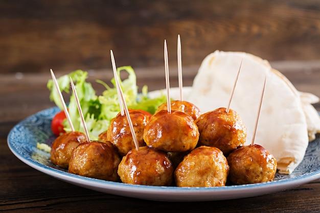 木製のテーブルにモロッコ風の野菜とピタパンを添えたプレートに甘酸っぱいglのミートボール。