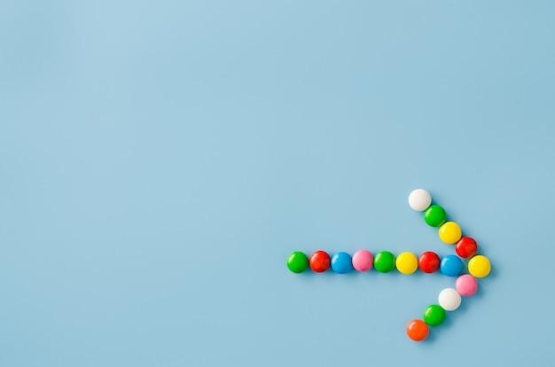 青色の背景に色付きのgl薬とチョコレート菓子のポインター矢印。
