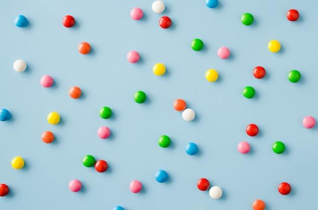 色付きのgl薬とチョコレート菓子の背景。散乱色とりどりのキャンディ。