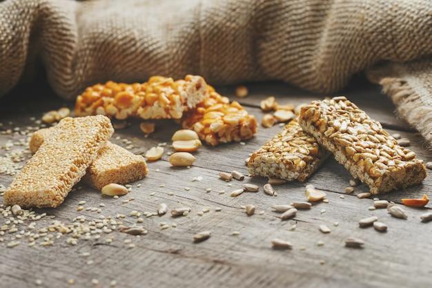黄麻布を使用したコジナキの盛り合わせ。カントリースタイル。ヒマワリ、ゴマ、ピーナッツの種子からのおいしいお菓子。光沢のあるgl薬で覆われています。