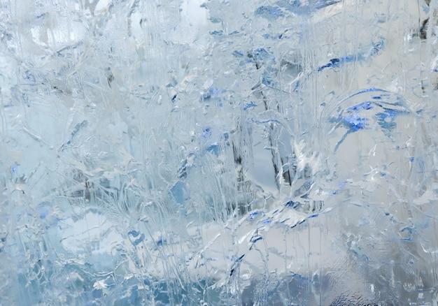 面白い絵や模様が描かれた氷河の透明な氷の壁。冬の背景。