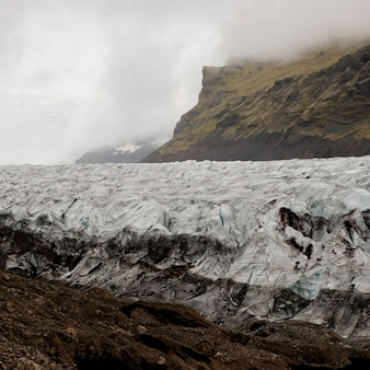 Glacier in cloudy mountain valley