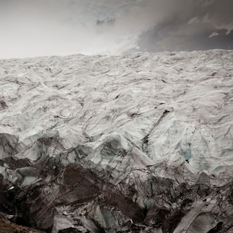 Glacier ice field in misty mountain valley