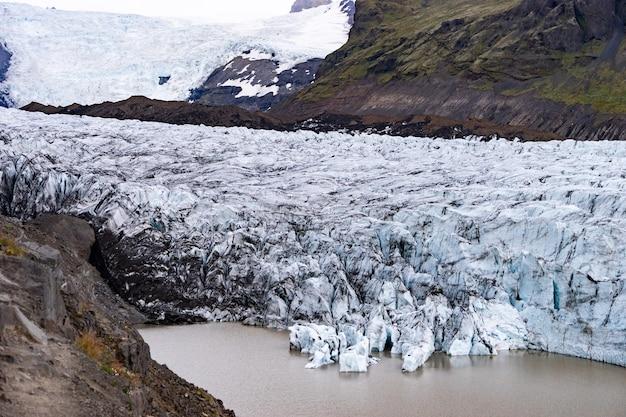 Ледник с пеплом во льду с талой водой и исландский пейзаж