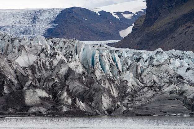 Ледник с пеплом во льду с талой водой и исландский пейзаж.