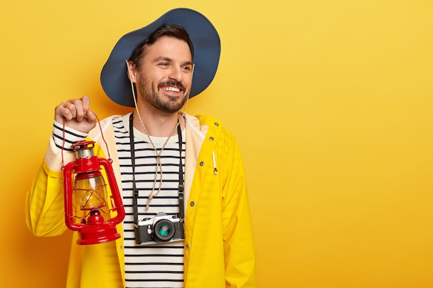 Glad active male holds gas lamp, has walk in forest, wears retro camera on neck, looks with smile aside, wears hat and raincoat, poses over yellow wall