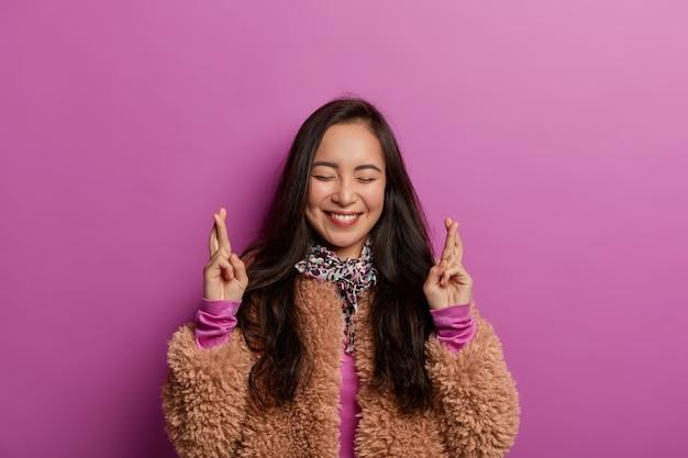 嬉しい愛らしいアジアの女性は特別な瞬間を待って、指を交差させ続け、より良いことを祈り、目を閉じて歯を見せる笑顔