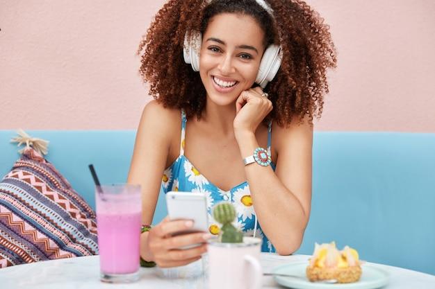Довольная очаровательная темнокожая женщина слушает музыку в наушниках, держит смартфон, сидит на удобном диване в кафе, пьет свежий коктейль.