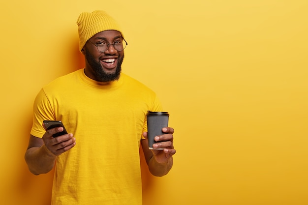 Glad african american man reads news feed in social networks, enjoys hot drink from disposable cup