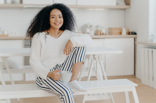 Glad african american woman holds cup of hot beverage leans at knee wears white stylish jumper and striped trousers