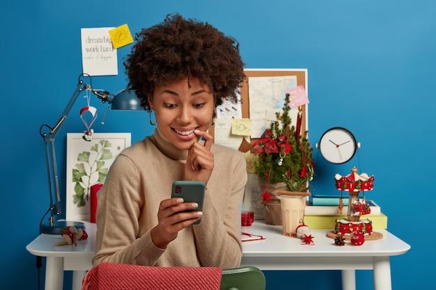 기쁜 아프리카 계 미국인 여성이 스마트 폰 디스플레이를 기꺼이 바라보고 그룹 동료에게 메시지를 보내고 온라인 채팅에서 시험 준비를 논의합니다.
