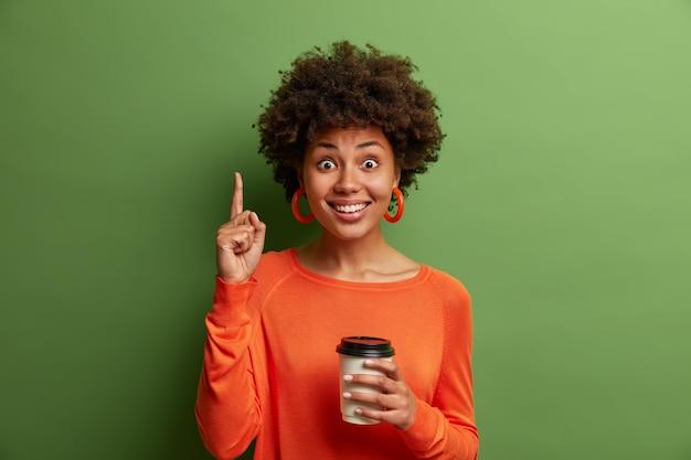 Felice donna afroamericana con i capelli ricci, beve caffè da asporto, punta l'indice sopra, soddisfatta di visitare un'accogliente caffetteria, ha un sorriso a trentadue denti, consiglia qualcosa, posa su un muro verde