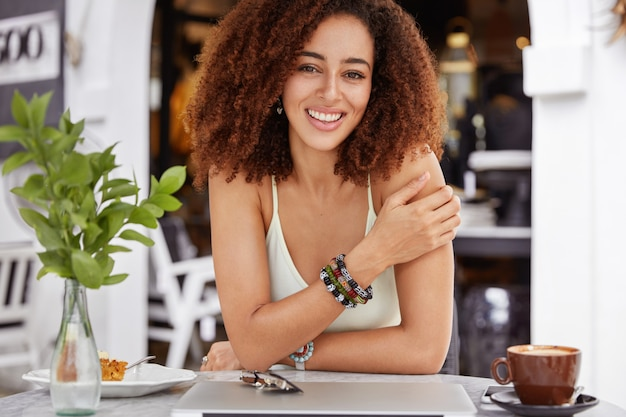 Glad african american young woman rests alone in coffee shop, has delighted look, rests after work on laptop computer, has positive expression.