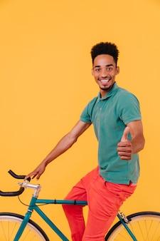 親指を立ててポーズをとるうれしいアフリカのサイクリスト。自転車に座っているカジュアルな緑のtシャツを着た黒人男性の屋内ショット。