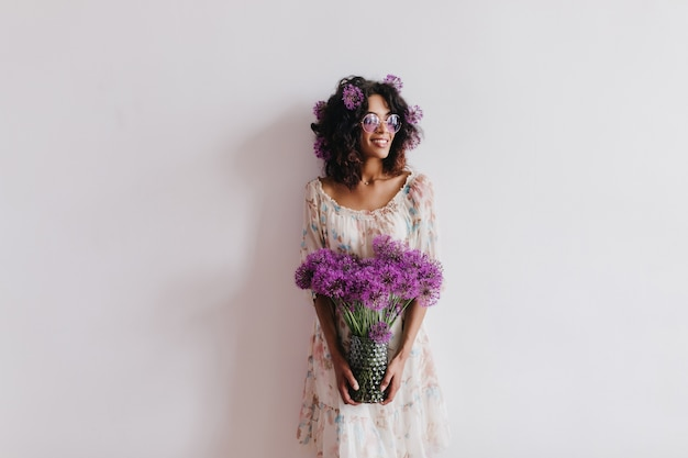 Glad african girl holding vase of flowers and smiling. indoor portrait of charming brunette woman in dress posing with alliums.