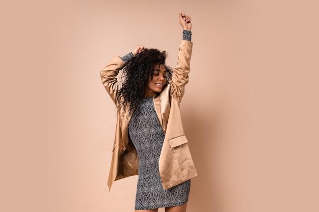 Felice donna africana con perfetti capelli ricci in elegante abito di paillettes ballando. atmosfera di festa.