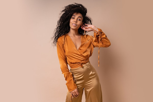 캐주얼 오렌지 블라우스와 베이지 색 벽에 포즈 황금 바지에 완벽 한 곱슬 머리를 가진 기쁜 아프리카 여자.