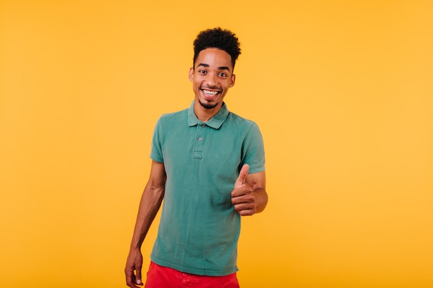 Glad african young man in green attire smiling. good-humoured black male model laughing.