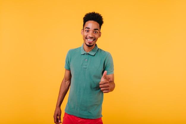 녹색 복장 웃 고있는 다행 아프리카 젊은 남자. 웃고있는 기분 좋은 흑인 남성 모델.