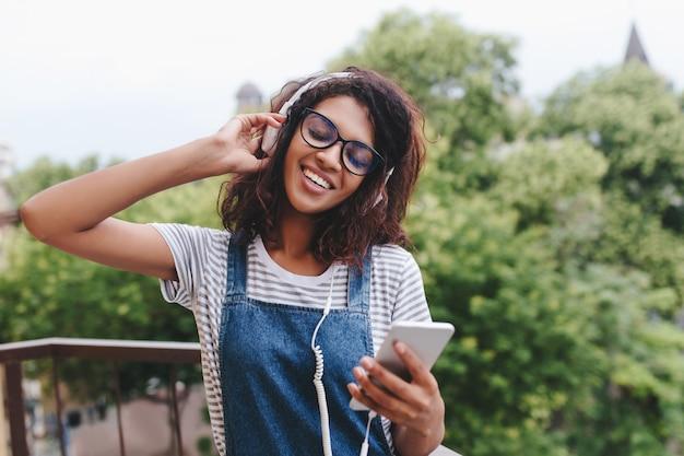 Счастливая африканская молодая женщина в полосатой рубашке стоит на дереве и слушает песню с закрытыми глазами