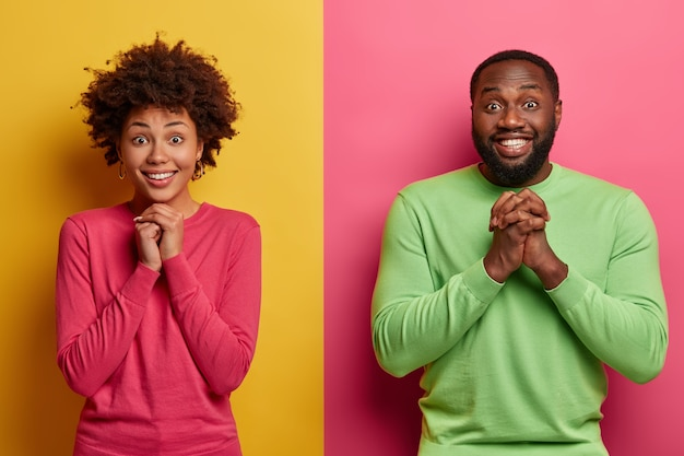 Felice fidanzato afroamericano e fidanzato tengono le mani unite nel gesto di preghiera, anticipano risultati importanti, stanno uno accanto all'altro contro due muri colorati, sorridono ampiamente, si sentono felici
