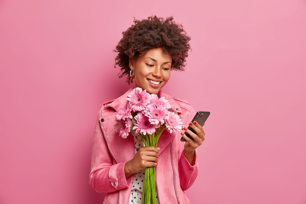 Glad afro american lady in stylish clothes checks messages online gets congratulations on birthday holds beautiful bouquet of gerberas has happy mood isolated over pink wall