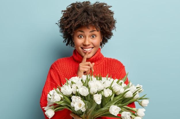 곱슬 머리를 가진 기쁜 아프리카 계 미국인 여성은 빨간 점퍼를 입고 조용히 몸짓과 미소를 지으며 파란색 벽 위에 고립 된 흰색 봄 튤립을 보유하고 있습니다. 누가 꽃을 선물했는지 말하지 않을게