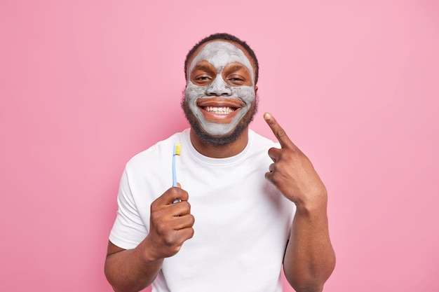 Glad afro american man smiles happily cares about teeth holds toothbrush applies beauty clay mask on face