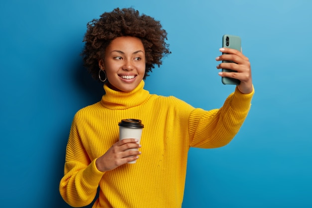 Glad afro girl records video online, takes selfie on mobile phone, extends arm with modern gadget, photographs herself, holds paper cup with coffee
